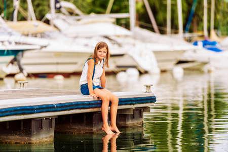 Schattige kleine jongen meisje rust aan het meer, zittend op de pier