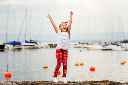 9 year old: Happy girl  9 year old having fun outdoors, playing by lake on a nice warm sunny evening, wearing white t-shirt and shoes, red polka dot trousers and headband. Image taken at Lake Geneva, Switzerland