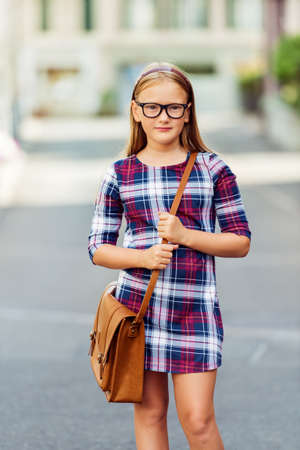 9 year old: Pretty little 9 year old girl walking back to school, wearing glasses, plaid dress and brown leather bag