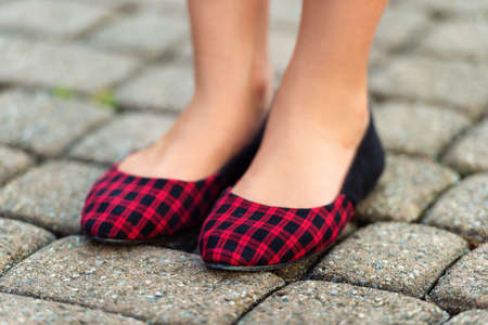 Close up of red and black plaid ballerinas on childs feet