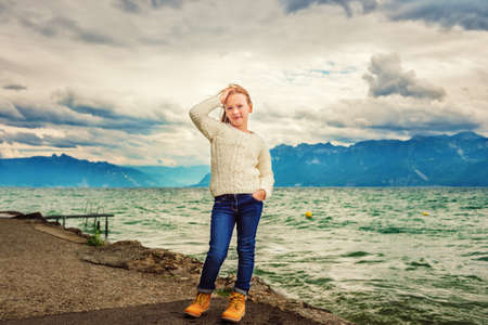 Cute little girl of 8 years old playing by the lake on a very windy day, wearing warm white knitted pullover, arms wide open, toned image Stock Photo