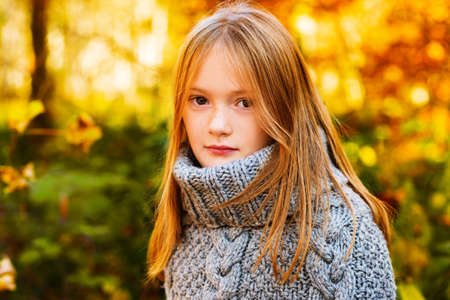 Outdoor portrait of a cute little girl in autumn forest, wearing grey knitted poncho Stock Photo