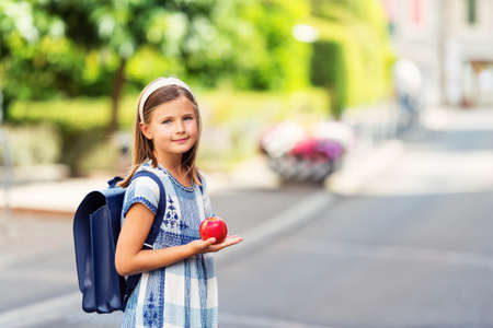 9 year old: Pretty little 9 year old girl walking back to school, wearing blue vintage backpack, holding red apple