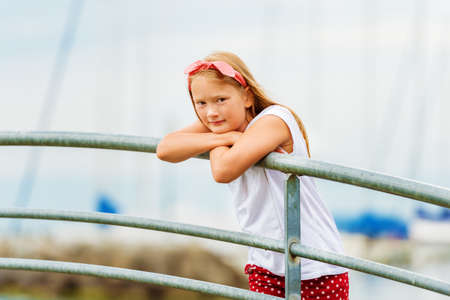 9 year old: Outdoor portrait of a cute 9 year old girl on a bridge at a port, leaning on the railings with boat on background Stock Photo