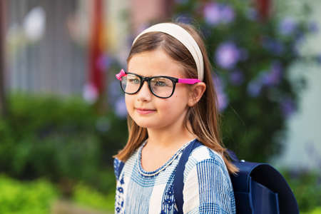 9 year old: Pretty little 9 year old girl walking back to school, wearing glasses and blue backpack