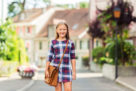 9 year old: Pretty little 9 year old girl walking back to school, wearing plaid dress and brown leather bag
