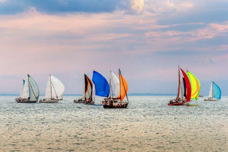 spinnaker: Colorful yachts at sailing competition on Lake Geneva at sunset on a beautiful summer day Stock Photo