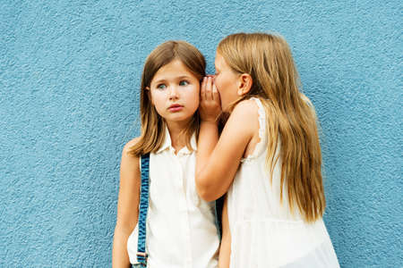 blab: Two cute little girls sharing secrets, standing in front of blue wall at school backyard Stock Photo