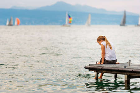 Cute little kid girl resting by the lake, sitting on pier, splashing water with her feet, back view