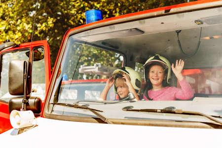 Twee schattige kinderen spelen in brandweerwagen, doen alsof ze brandweerlieden, open deuren dag op brandweerkazerne zijn. Toekomstige beroep voor kinderen. Educatief programma voor schoolkinderen