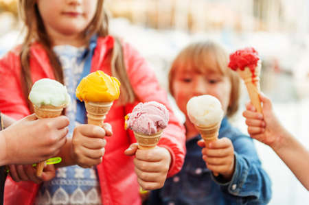 5 corns of colorful ice cream holding by kids