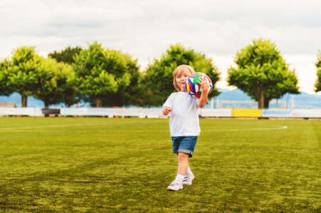 3 year old: Adorable little 3 year old boy playing soccer on the stadium