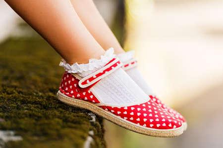 Close-up van de rode polka dot schoenen op de voeten van het kind