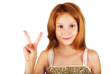 9 year old: Studio shot of adorable little 9 year old girl with red hair, showing peace sign