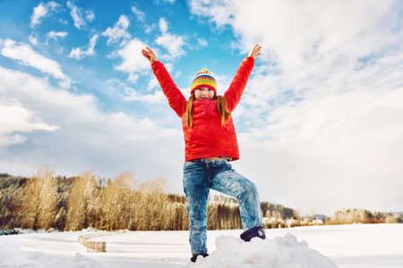 arms wide open: Little girl wearing red jacket and colorful hat, playing with snow in winter time, arms wide open Stock Photo