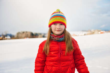 january 1: Little girl wearing red jacket and colorful hat, playing with snow in winter time