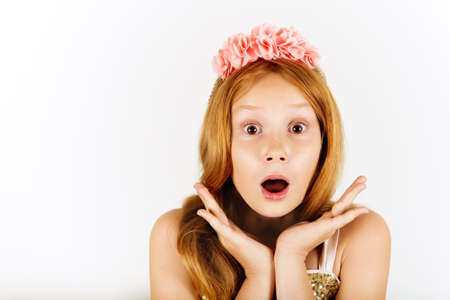 Headshot of pretty surprised little girl with red hair, wearing headband. Hands on cheeks looking at the camera with astonished or shocked expression, mouth wide open. Human facial expressions Stock Photo