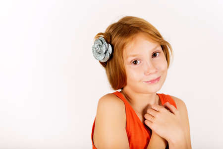 9 year old: Studio shot of adorable little 9 year old girl with red hair, wearing orange top