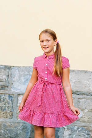 8 year old: Outdoor portrait of cute little 8 year old girl, wearing red mary jane dress