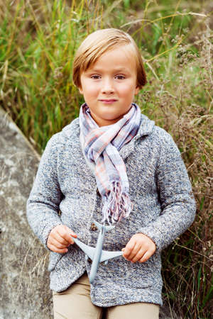 knitted jacket: Outdoor fashion portrait of adorable little boy wearing  knitted jacket and stylish scarf, holding small toy airplane Stock Photo