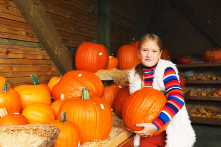niños rubios: Adorable little girl of 8-9 year old choosing halloween pumpkin on farm market
