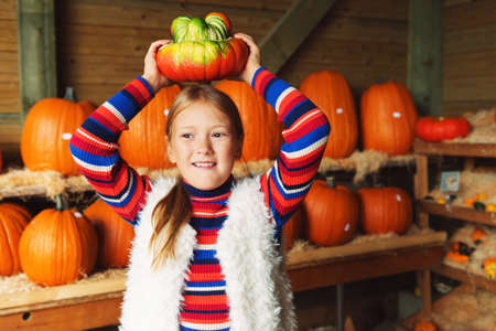 expressive face: Adorable little girl of 8-9 year old choosing halloween pumpkin on farm market, having fun with unusual different kind of pumpkins Stock Photo