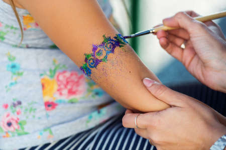 Little girl getting glitter tattoo at birthday party