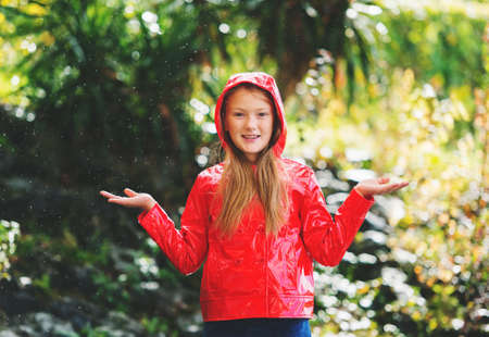 9 year old: Adorable little 9 year old girl playing under the rain in the park wearing red vinyl jacket