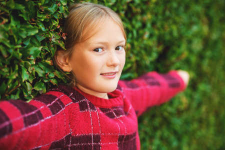 Outdoor close up portrait of cute little 8-9 year old little girl wearing bright red pullover, standing next to green bushes, arms wide open