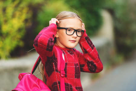 9 year old: Outdoor portrait of a cute little 9 year old girl, wearing red pullover, glasses and pink backpack Stock Photo