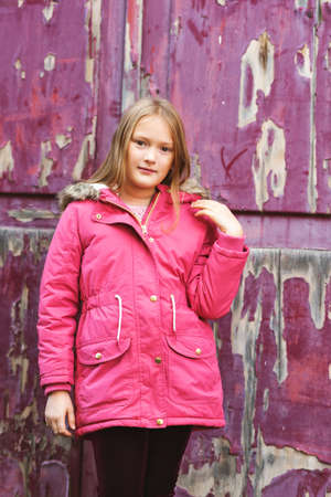 9 year old: Outdoor vertical portrait of cute 9 year old little girl wearing pink winter coat, standing next to purple background Stock Photo