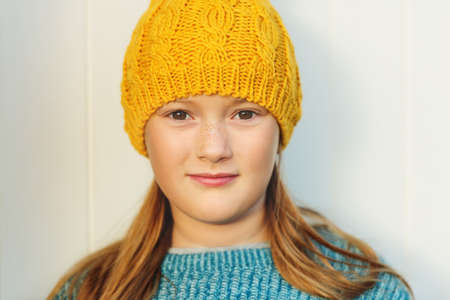 9 year old: Close up portrait of cute 9 year old little girl wearing yellow hat, standing against white background Stock Photo