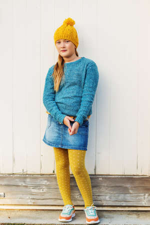 9 year old: Outdoor fashion portrait of cute 9 year old little girl, wearing yellow hat, blue pullover, denim skirt and polka dot tights