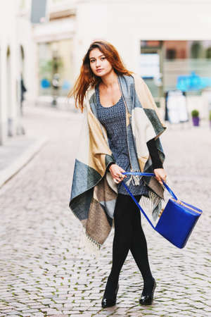Outdoor fashion portrait of young 20 year old girl wearing grey and beige scarf jacket and blue bag Stock Photo