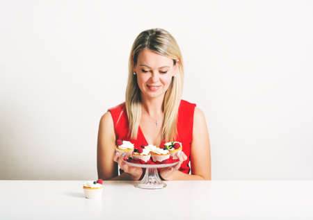 Beautiful young blond woman sitting at the table, holding home made cupcakes