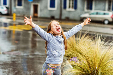 arms wide open: Adorable little girl catching rain drops with her tongue, arms wide open