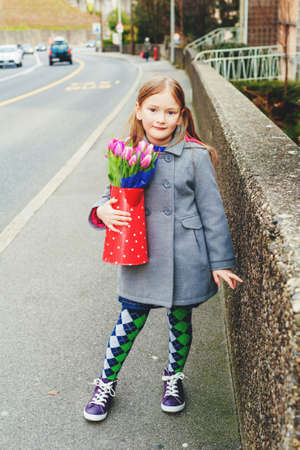 purple shoes: Spring portrait of 7 year old girl holding polka dot watering can with fresh pink tulips, wearing grey coat, green tights and purple shoes