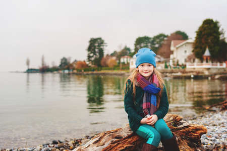 Little girl resting by lake Geneva in winter time, wearing warm hat and scarf