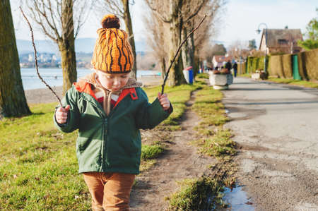 3 year old: Cute 3 year old little boy playing outdoors on sunny early spring day, wearing green jacket and orange hat