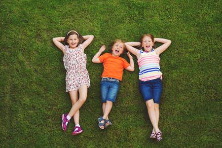 Gelukkige kinderen met plezier buiten. Jonge geitjes die in de zomer park. Weinig jongen en twee meisjes die op groen vers gras