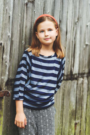Outdoor portrait of cute little 8-9 year old girl with brown hair, wearing stripe top, standing against old wooden background Stock Photo