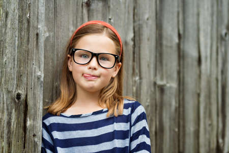 Outdoor portrait of a cute little 9 year old girl wearing eyeglasses Stock Photo