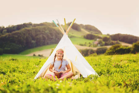 Cute little girl having fun outdoors, playing with tambour, sitting next to teepee