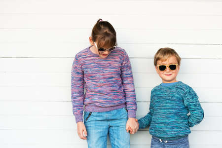 pullovers: Fashion kids outdoors, wearing knitted pullovers and sunglasses, holding hands