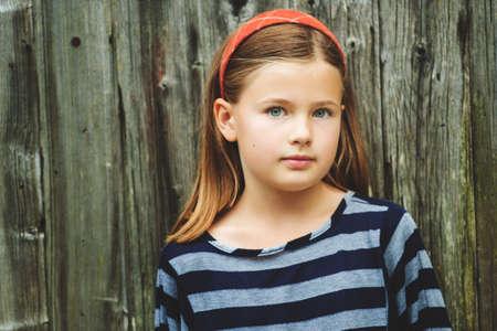 Outdoor portrait de mignon petit 8-9 ans, fille aux cheveux bruns, portant haut de bande, debout contre les vieux fond en bois