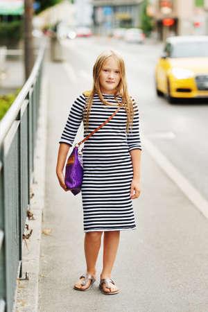 Outdoor fashion portrait of a pretty little girl, wearing stripe marine dress and purple dress