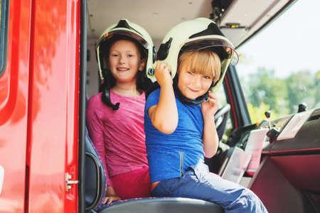 Twee leuke jonge geitjes die in brandvrachtwagen spelen, die brandbestrijders beweren te zijn, openen deurendag bij brandweerkazerne. Toekomstig beroep voor kinderen. Educatief programma voor schoolkinderen
