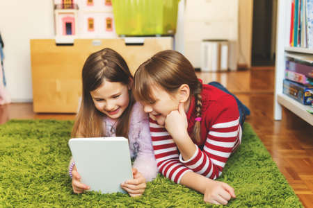 vivacious: Two cute little girls playing on digital tablet pc, laying on green carpet in kids room