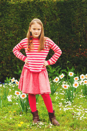 Cute little girl of 7-8 years old playing in the spring park between daffodils flowers, wearing stripe pullover, red skirt and tights, brown leather boots