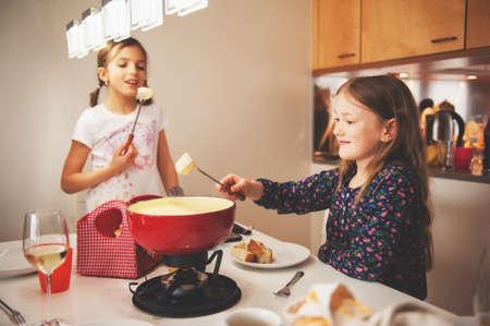 Twee jongen meisjes eten Zwitserse fondue voor het diner